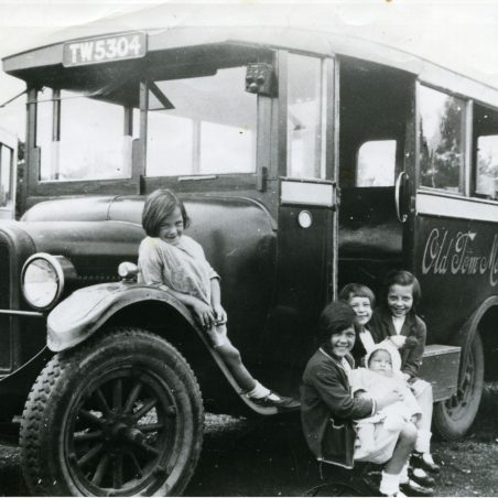 Old Tom Motor Services in yard with Carter children, ready to travel to Wickford market (1927). Left to right: Edna, Eileen (holding baby Marjorie), Joan and Vera.   Ann and John Rugg