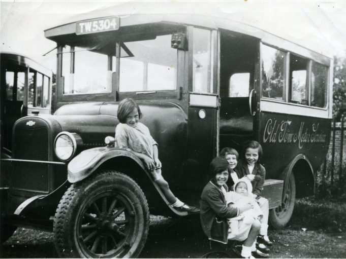 Old Tom Motor Services in yard with Carter children, ready to travel to Wickford market (1927). Left to right: Edna, Eileen (holding baby Marjorie), Joan and Vera. | Ann and John Rugg