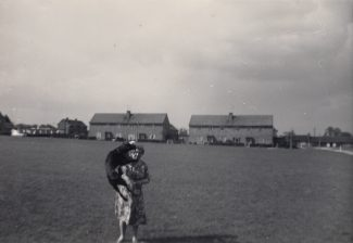 1961 Mum playing with Rex on field with Cromer Avenue Left hand side in distance with row of garages. OAP bungalows at end of Bushy Mead on Right | Patsy Mott (née Tyler)