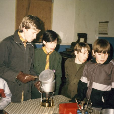 6th Laindon Scout Troop trying out various stoves in St Nicholas Hall, approx. 1984.  Note the old organ in the background.  The hall was so cold in winter that most scouts kept their coats on.