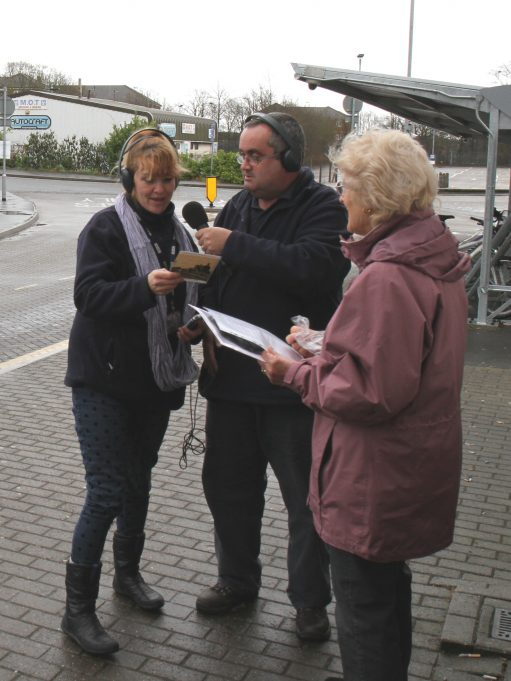 Liana reading out the next clue from the back of a picture postcard of Laindon Station.   Colin Humphrey.