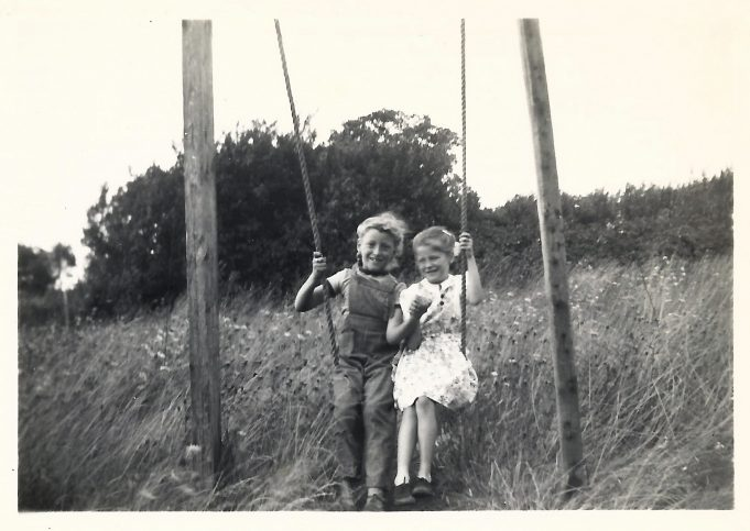 Nina and Joan on the swing at Spion Kop 1954.  I loved the grass, wild flowers and trees that were just outside out back door.   The western end of Bourne Avenue now stands on this spot where our swing had once been. | Nina Humphrey