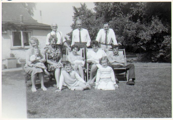 The Peters family in Dunton Road 1964. Bertie Peters back row far left with Phyllis infront of him.  Son Claude in the deckchair middle row far right.  His wife Anne beside him.  Daughter Barbara in deckchair between Phyllis and Anne.  Barbara's husband Derek Smith back row far right.  The other couple are Bertie's sister and brother-in-law.  Plus various grandchildren. | Nina Humphrey(née Burton)