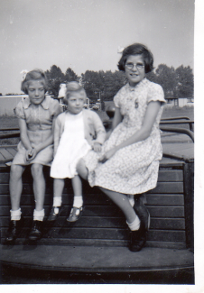 Winifred Archibald with her two younger sisters, Joan and Vanessa, on the merry go around